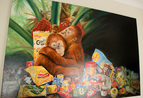 Painting depicting orang-utans and all the common supermarket products that contain palm oil from unsustainable sources, Jo Frederiks, vegan artist, animal activist, using art to raise awareness of animal suffering and inspiring change to a cruelty-free l