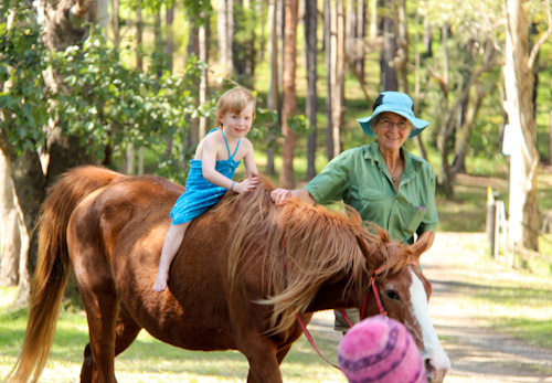 Delaney riding a horse with Nan Nicholson, The Channon, August 2014