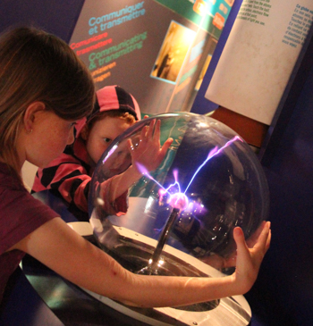 Playing with a plasma ball at the Microcosm exhibition, CERN, Geneva, Switzerland, September 2014