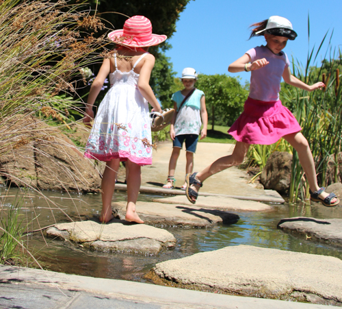 Jumping over stepping stones, Hunter Valley Gardens, NSW, January 2015