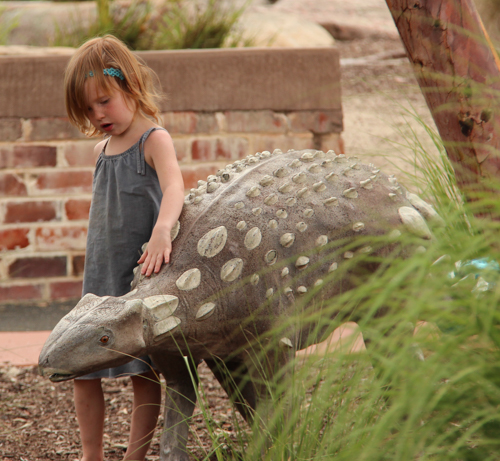 Lana petting a dinosaur, Bathurst's Adventure Playground, NSW, January 2015