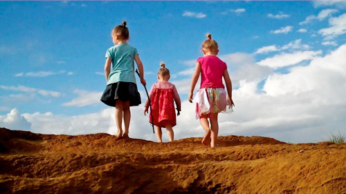 Aisha, Brioni and Calista climbing up the top of a sandhill, August 2011