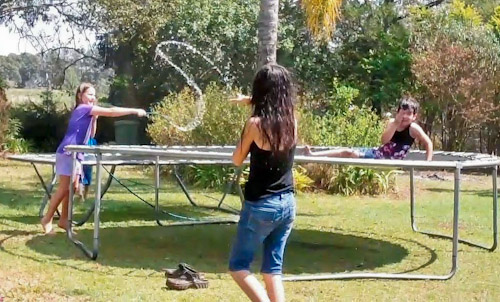 Girls playing with trampoline and hose, September 2011
