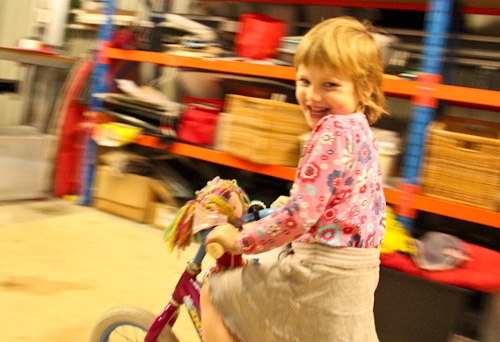 Calista riding her bike with a doll, July 2012