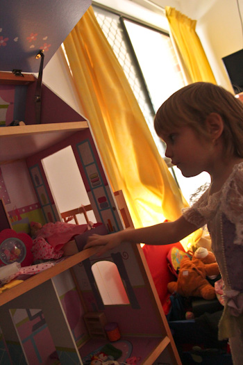 Calista in front of a doll-house, August 2012
