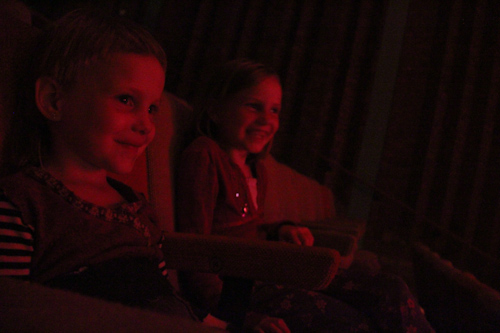 Calista and Aisha laughing as they watch Jeff Achtem's Sticks, Stones and Broken Bones shadow puppetry show, Ulverstone, Tasmania, January 2013